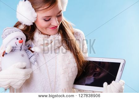 Young woman with computer tablet and little snowman. Happy girl in white sweater pullover and earmuffs holding pc ebook. Technology and winter fashion.