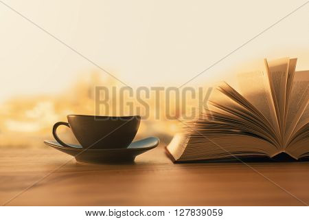 Black coffee cup and open book on wooden table with blurry city in the background