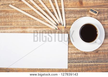 Blank envelope coffee pencils and sharpener on wooden desktop. Topview Mock up