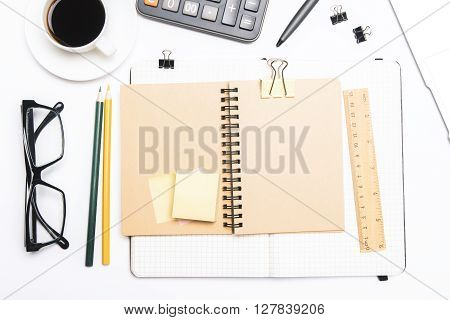 Topview of white desktop with coffee spiral notepads glasses calculator and other office tools