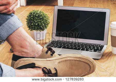 Male feet on wooden floor next to blank notebook screen coffee plant and other items. Mock up