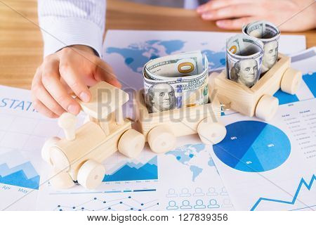 Topview of male hand and money filled wooden train placed on business diagrams