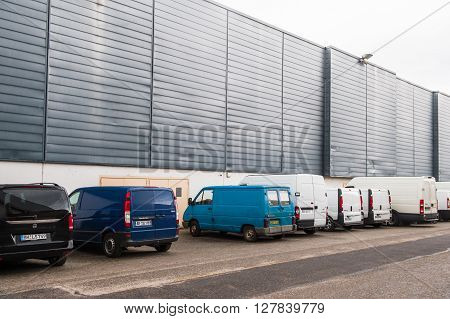 STRASBOURG FRANCE - APR 24 2016: Diverse transportation vans parked near and industrial hall
