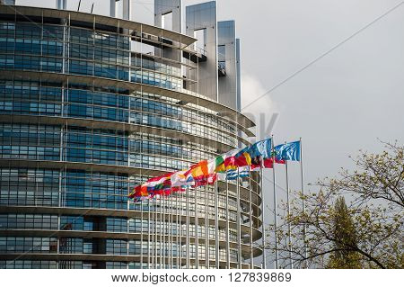 STRASBOURG, FRANCE - APR 24 2016: European Parliament building with all European union flags waving in wind on a spring day in Strasbourg France Alsace