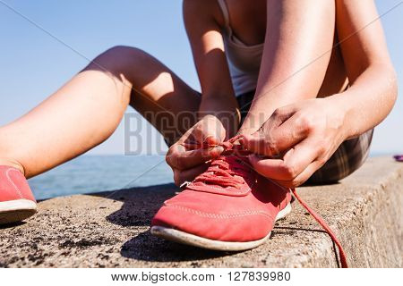 Outdoor relax holidays nature concept. Young girl tying shoelace. Lady sunbathing on coast making a knot.
