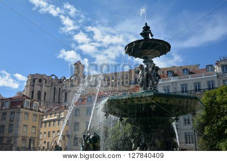Beautiful 19th century fountain in the center of Rossio Square with ruined Carmo Convent in the background destroyed by the great earthquake of 1755