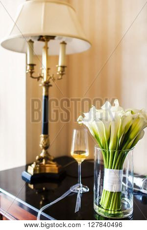 Wedding bouquet with white callas in the vase on the table