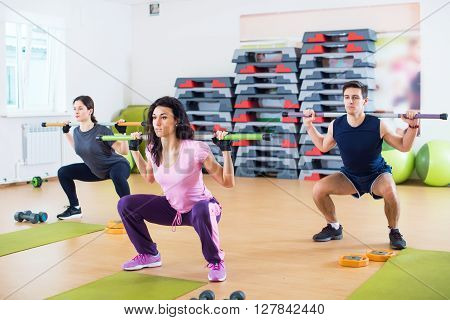 People exercising in gym doing squats working out with barbells in fitness club
