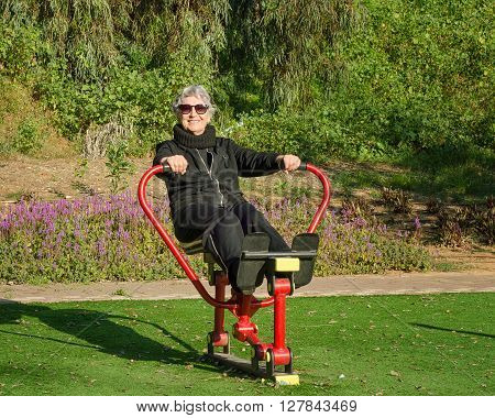 76-year-old woman in sunglasses tries out rowing trainer in her local park. Grey-haired woman in black sport suit is working out at outdoor gym. She strengthens her upper body and core muscles. Promote health and well-being lifestyle concept. Bright sunny