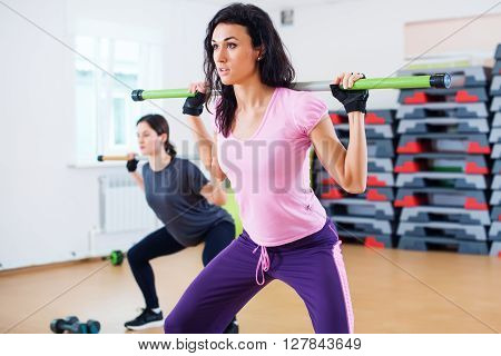 Group of people excercising with bars in gym doing squatting with a barbell at fitness club.