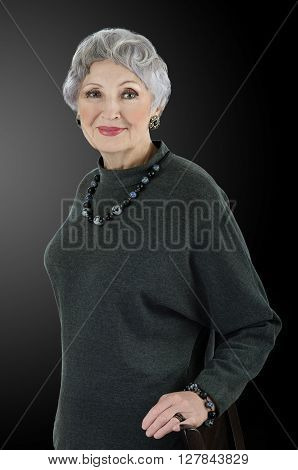 Portrait of stunning 76-year-old woman wears snowflakes obsidian sodalite beads necklace with bracelet. Grey haired woman is clothed in dark grey wool dress. Upper body vertical shot on black background