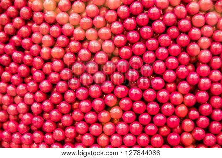Red, cherry flavored candy drops in a bulk food bin