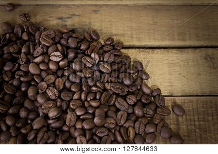 Coffee beans on grunge wooden background Fresh coffee beans on wood.