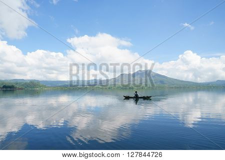 Unrecognizable man fishing in the middle of the Lake Batur overlooking Mount Batur suring cloudy bluesky in Bali Indonesia.