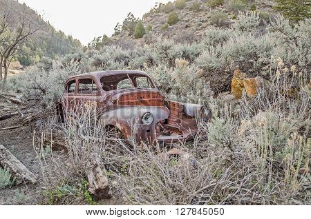 HELPER, UTAH - APRIL 20: Vintage automobile in need of a hood, an engine, and other parts sits abandoned in a rural area APRIL 20, 2016 near HELPER, UT.
