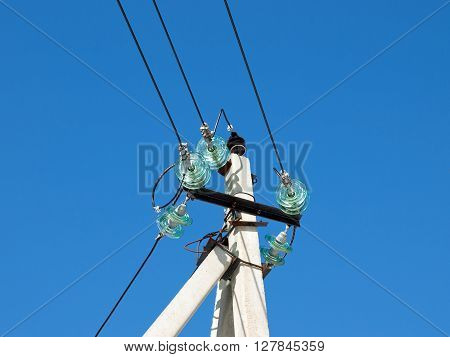 Pillar of electricity transmission line with transparent insulators. Photographed close-up against the blue sky
