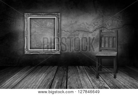 Picture frame and wood chair in interior room with gray stone wall.