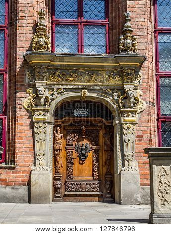Old vintage wooden door decorated with sculptures and with door knocker in the form of a eagle