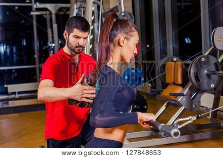 fitness, sport, training and people concept - Personal trainer helping woman working with in gym.