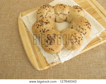Homemade roll wreath with flax seeds on wooden board