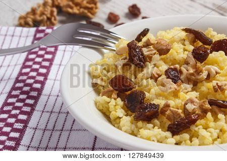 Fresh cooked millet groats with raisins and walnuts on white plate concept of healthy food nutrition and nutritious breakfast