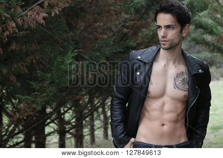 sexy male posing shirtless in the wood