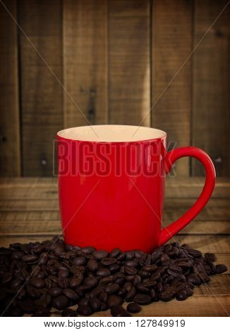 coffee beans and red cup on the wooden table Concept filter sepia