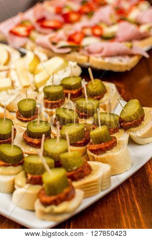 Canapes with sausage and gherkin wood table