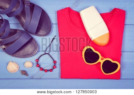 Vintage photo Clothing for woman and accessories for vacation and summer on blue boards sunglasses sun lotion leather sandals shirt