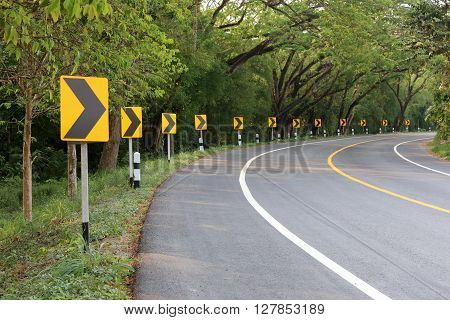 The road curve with street signs reflex light. At night you can see the signs more clearly.