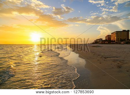 FORT MYERS BEACH, USA - MAY 12, 2015: The sun setting above the Gulf of Mexico with the sea on the left and the beach with buildings on the right.