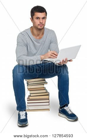 Young man looking for information in books and on the computer isolated