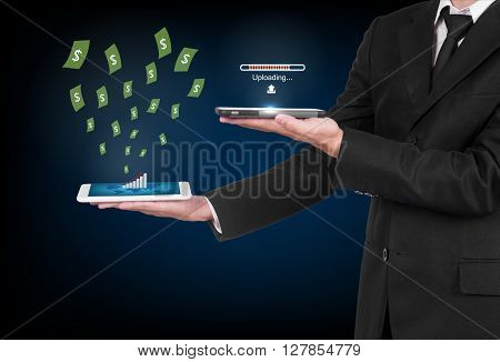 Businessman With Modern Mobile Phone Uploading Data And  Money Flting Out In His Hand