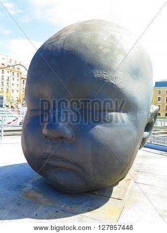 Madrid Spain April 7 2016: Madrid Atocha Railway station forecourt sculpture of childs head. Madrid Spain April 7 2016
