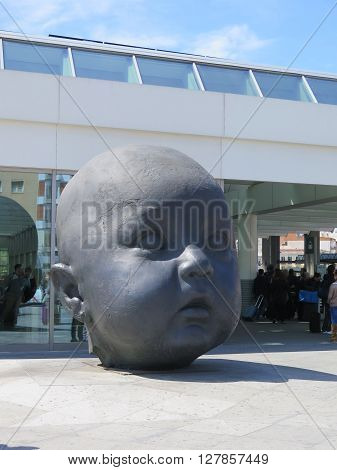 Madrid Spain April 7 2016: Madrid Atocha Railway station forecourt sculpture of childs head. Madrid Spain April 7 2016