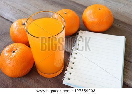fresh orange fruit placed on wooden floor and have juice in glass for concept of healthy eating.