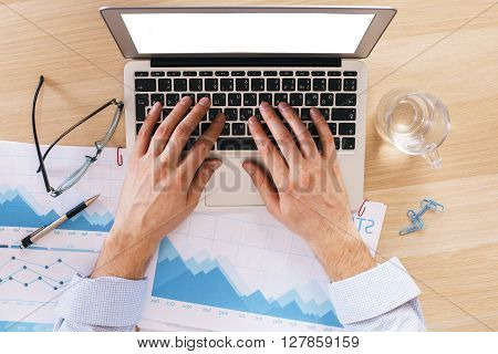 Topview of hands using laptop with blank screen on wooden desk with glaases business report and water. Mock up