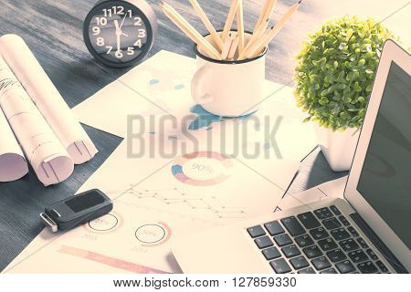 Topview of desktop with laptop business charts iron mug with pencils and other items. Toned image