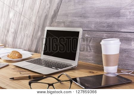 Sideview of wooden desktop with blank laptop screen croissant tablet and other items. Mock up