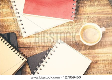 Topview of wooden desktop with notepads and coffee mug