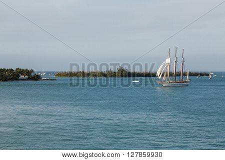 Schooner under sails sailing across a bay under beautiful skies