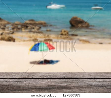 Wooden table top on blurred white sand beach and blue sea with parasol Can be use for display or montage your product