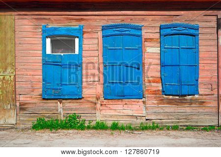 Old wooden window of slum house painted in red and blue color  in Astrakhan, Russia