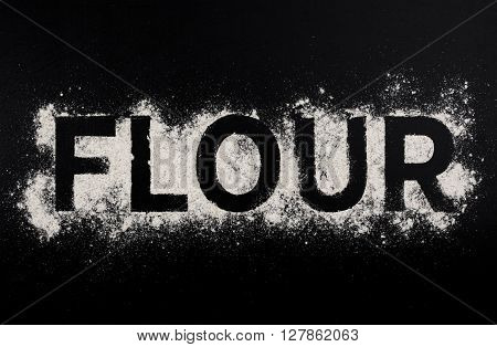 Word flour made from white flour on a dark table