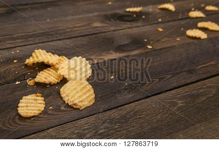 Potato chips on a wooden table. Homemade potato chips close up