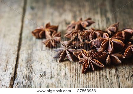 Star anise spice and fruit seeds on vintage wooden background. Close-up. Selective focus
