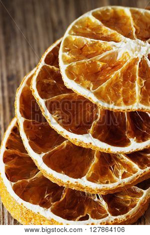 Slices of dried oranges on a vintage wooden background close-up. Dried fruits. Selective focus