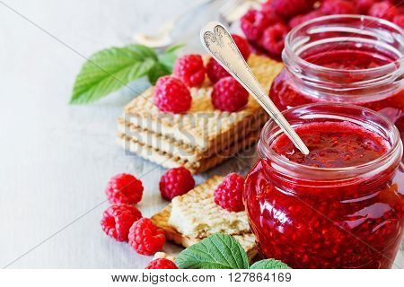 Raspberry jam in a glass jar and cookies on a white wooden table. Healthy breakfast concept. Bio healthy food. Organic fruit jam. Selective focus