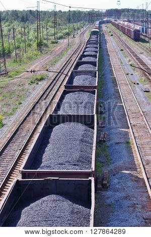 Wagons with coal and railroad tracks near forest in summer sunny day