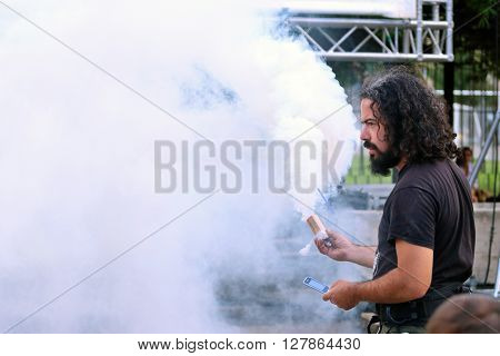 PERM RUSSIA - JUNE 5 2015: Man holding smoke flare at Perm Kaleidoscope Festival